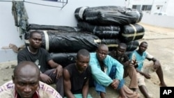 Ghanaian drug-runners sitting in front of bales of cannabis seized by the anti-drug section of the Ivorian gendarmerie in Abidjan (File Photo)