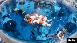 Steve Bowen is lowered into the Neutral Buoyancy Laboratory at Johnson Space Center to test spacewalk suits and tools for a mission to an asteroid.