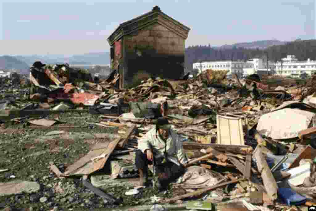 A tsunami survivor sits down in the rubble in Yamadamachi in Iwate Prefecture Monday, March 14, 2011, three days after a powerful earthquake-triggered tsunami hit the country's east coast. (AP Photo/The Yomiuri Shimbun, Takashi Ozaki) JAPAN OUT, CREDIT MA