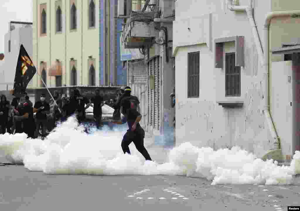 An anti-government protester throws a stone at riot police amid teargas fired by the police during clashes in the village of Diraz, west of Manama, Bahrain. Protests following the death of 20-year-old Fadhel Abbas threatened to sour a new attempt to restart negotiations between Bahrain's government, led by the ruling al-Khalifa family, and opposition groups.