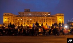 Demonstrators march in front of the government building during a protest in Bucharest, Romania, Feb. 4, 2017. On Saturday, thousands of Romanians took to the streets for a fifth consecutive day to protest a decree that waters down the country's anti-corru