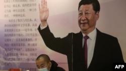 中國遼寧省瀋陽市的一家書店裡一名戴著口罩的讀者坐在中國國家領導人習近平的大幅畫像前。(2020年4月23日)