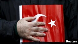 FILE - A supporter of Gulen movement holds a Turkey's national flag during a protest outside the Kanalturk and Bugun TV building in Istanbul, Turkey, Oct. 28, 2015.