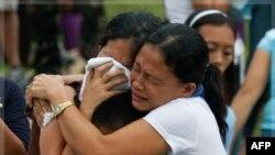 Thân nhân của các nạn nhân chết trong trận bão Washi đau buồn lúc các thị hài được chôn tập thể tại một nghĩa trang trong thành phố Iligan, miền nam Philippines