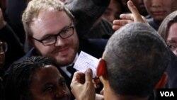Barack Obama lee una nota de protesta que le entregó un manifestante.