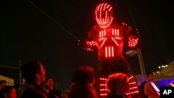 Young participants look at a performer wearing a luminous costume entertaining a crowd in Lisbon, Portugal, during the symbolic switching off of lights known as Earth Hour, March 28, 2015.