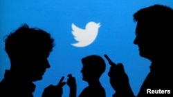 FILE - People holding mobile phones are silhouetted against a backdrop projected with the Twitter logo, Sept. 27, 2013.