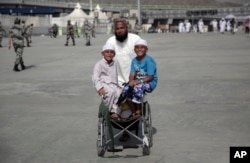 FILE - Two children pose for the camera while pushed by their father, who walks to cast stones at three huge stone pillars in the symbolic stoning of the devil, during the Hajj, outside the holy city of Mecca, Saudi Arabia, Sept. 3, 2017.