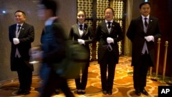 Chinese butler school graduates stand at attention outside the entrance to a conference in Beijing, Sept. 25, 2015.