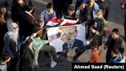 Bağdat'ın Tahrir Meydanı'nda protesto düzenleyerek Cumhurbaşkanı Erdoğan'ı karikatürize eden posteri yakan Iraklılar
