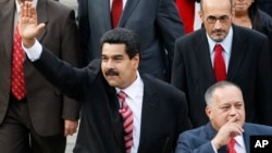 Venezuela's Vice President Nicolas Maduro, left, and Diosdado Cabello, president of Venezuela's National Assembly, gesture to supporters as they arrive at the National Assembly for the state-of-the-nation address in Caracas, Feb. 28, 2013.