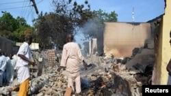 Des Nigérians sur les ruines d'un bâtiment au Nigéria, suite à un attentat de Boko Haram