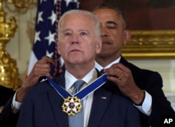 In this Jan. 12, 2017, file photo President Barack Obama presents Vice President Joe Biden with the Presidential Medal of Freedom during a ceremony in the State Dining Room of the White House in Washington.