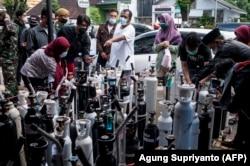Warga berkumpul untuk mengisi tangki oksigen di sebuah stasiun di Yogyakarta pada 14 Juli 2021. (Foto: AFP/Agung Supriyanto)