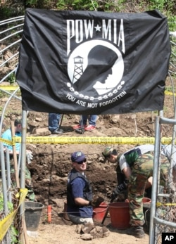 Bob Wood, Garden Valley, Calif., a members of the JPAC, Joint POW/MIA Accounting Command, bottom center, works as he digs to search for remains of U.S. soldiers killed during the 1950-53 Korean War in Hwacheon, South Korea, May 18, 2009.