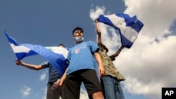 Young men wave national flags during a protest demanding the government release hundreds of protesters held in custody since 2018, in Managua, Nicaragua, March 16, 2019.