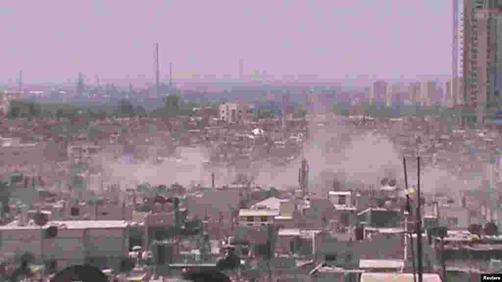 Asap mengepul dari kawasan Juret al-Shayah di kota Homs, Suriah (11/7).
