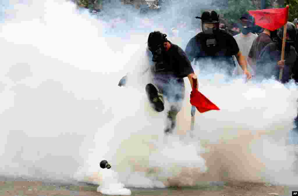 June 15: A demonstrator kicks a tear gas canister outside the Parliament in central Athens, during a rally against plans for new austerity measures.