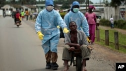Residents of the St. Paul Bridge neighborhood wearing personal protective equipment take a man suspected of having Ebola to the Island Clinic in Monrovia, Liberia, Sept. 28, 2014.