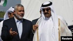 ນາຍົກລັດຖະມົນຕີຂອງກຸ່ມຫົວຮຸນແຮງ Hamas ທ່ານ Ismail Haniyeh (ຊ້າຍ) ແລະ ກະສັດ Sheik Hamad bin Khalifa al-Thani ຂອງກາຕາ ໄປເຖິງບ່ອນຈັດພິທີວາງສີລາເລີກ ຂອງໂຄງການ Hamad, ຊຶ່ງເປັນໂຄງການພັດທະນາຄຸ້ມຢູ່ອາໄສ ໃນ ເມືອງ Khan Younis ໃນພາກໃຕ້ຂອງເຂດກາຊາ, ວັນທີ 23 ຕຸລາ, 2012.