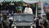 Muhammadu Buhari yana zaga dandali cikin mota tare da manyan jami'an tsaron kasa domin gaida jama'a da kuma sojojin da suka yi faretin karrama sabon babban kwamandan nasu