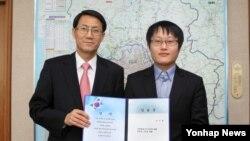 김성렬 한국 경기도 행정1부지사(왼쪽)로부터 임명장을 수여받는 탈북자 출신 정규직 공무원 1호 이수혁씨.