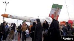 En esta foto de archivo del 11 de febrero de 2016 se ve gente alrededor de un modelo del cohete que transporta un satélite Simorgh, en Teherán, Irán.