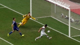 Iran's Reza Ghoochannejhad, right, scores against Bosnia during their match at the Fonte Nova arena in Salvador, June 25, 2014.