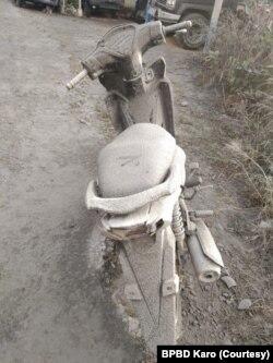 Sebuah sepeda motor di Desa Gung Pinto, Kecamatan Naman Teran, Kabupaten Karo, Sumut yang diselimuti abu vulkanik dari Gunung Sinabung, Sabtu 8 Agustus 2020. (Courtesy: BPBD Karo)