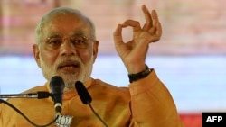 FILE - Indian Prime Minister and Bharatiya Janata Party leader Narendra Modi gestures as he speaks during a public rally ahead of the Maharashtra state election in Mumbai, October 2014.