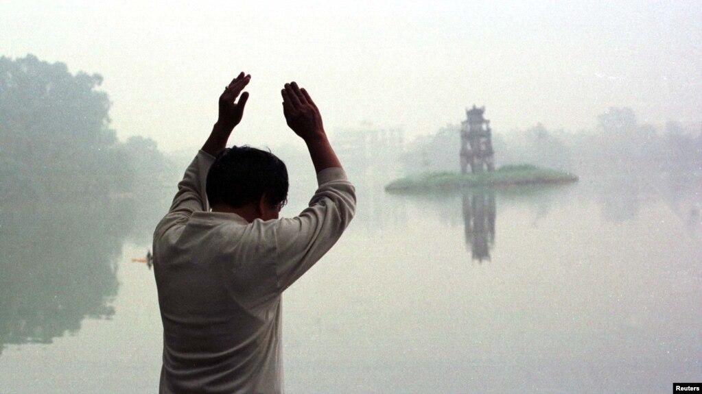Hình ảnh Hồ Hoàn Kiếm mờ ảo trong một sáng Chủ Nhật khi người dân đi tập thể dục