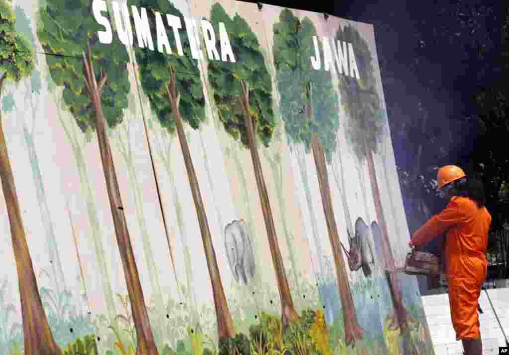 一位绿色和平活动人士在雅加达举行的一次反破坏森林的示威期间用电锯切割象征印尼森林的木墙。
