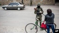 Proruski separatista proverava dokumenta na kontrolnom punktu u Slavjansku, u istočnoj Ukrajini