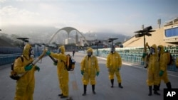 Health workers get ready to spray insecticide to combat mosquitoes in Rio de Janeiro at the 2016 summer games. The insects transmit the Zika virus. (AP File Photo/Leo Correa)