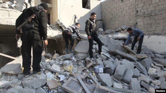 Free Syrian Army fighters and civilians search for bodies under rubble after an air strike by a fighter jet loyal to Syrian President Bashar al-Assad in Aleppo's al-Marja district December 31, 2012.