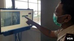 Petugas Kantor Kesehatan Pelabuhan Kelas 1 Surabaya menunjukkan tampilan monitor dan suhu tubuh penumpang yang melewati pintu kedatangan luar negeri (foto Petrus Riski-VOA).