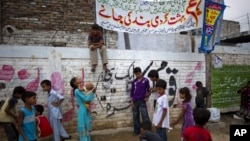 Pakistani Christian children play under a banner condemning the arrest of a Christian girl in Islamabad, Pakistan, Aug. 21, 2012.