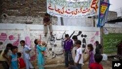 Anak-anak Kristen Pakistan bermain sambil membawa spanduk mengecam penahanan seorang anak perempuan atas tuduhan menghina al-Quran (21/8).