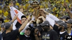 金州勇士队6月12日击败克里夫兰骑士队,赢得NBA冠军,球员、教练和球队老板高举奖杯