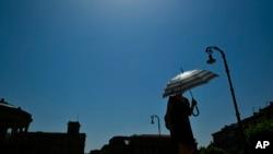 စပိန္ႏိုင္ငံ Pamplona ၿမိဳ႕မွာ ေနပူထဲ ထီးေဆာင္းထားတဲ့ အမ်ိဳးသမီးတဦး။ (ဇြန္ ၂၈၊ ၂၀၁၉)