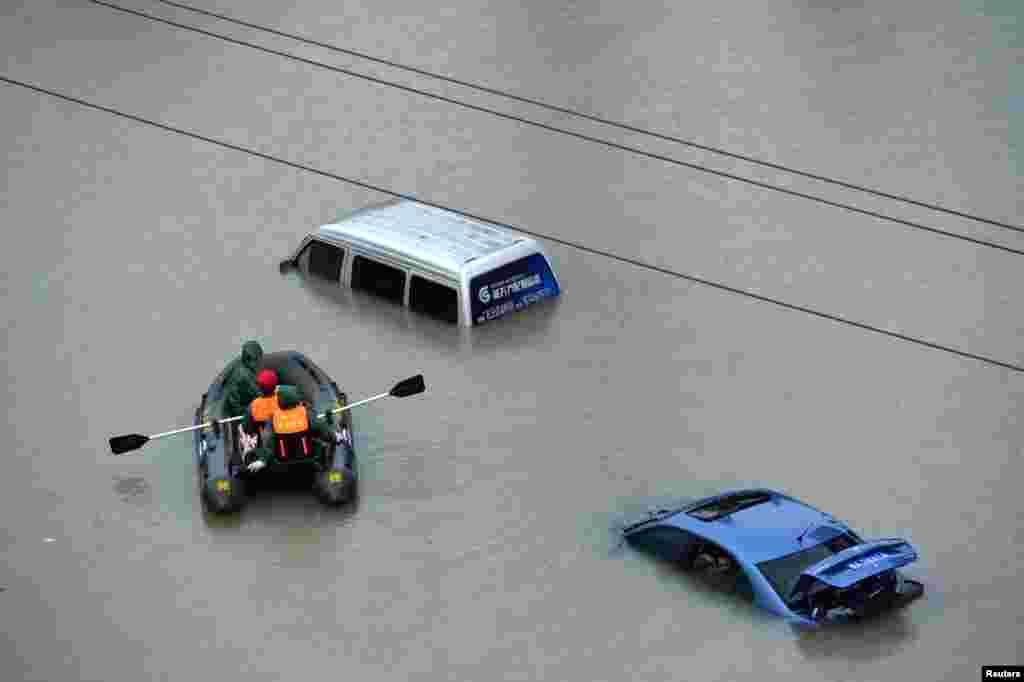 A rescue boat approaches a submerged car on a flooded street after heavy rainfall in Guiyang city, Guizhou province, China.