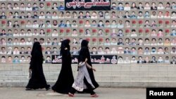 FILE - Shi'ite Muslim women walk past a wall with portraits of the deceased, who were killed in a bombing in a residential area in March 2013, during the Shi'ite Youm Ali procession in Karachi, Pakistan, June 27, 2016.