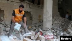 یکی از اعضای صلیب سرخ جهانی در حال بررسی مواد و لوازم پزشکی باقی مانده در ساختمانی که هدف حمله هوایی قرار گرفته است - آرشیو