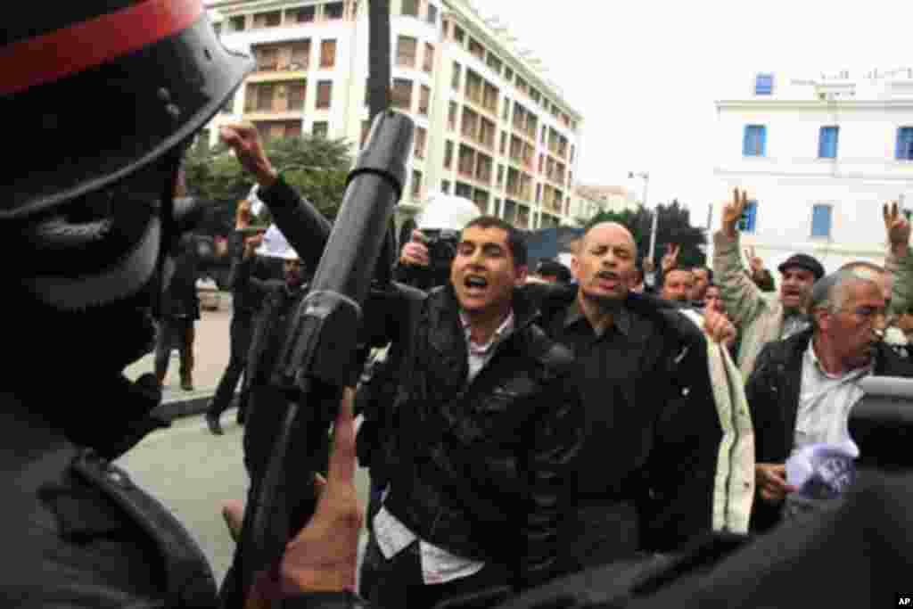 Un agent de la police anti-émeute face à des manifestants à Tunis, le 18 janvier 2011
