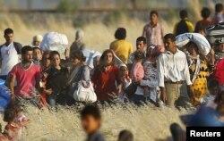 Sírios Curdos de Kobani caminham para a fronteira de Suruc, na província de Sanliurfa, Turquia, Junho 26, 2015.