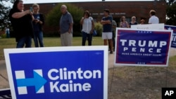 Early voters stand by campaign signs as they wait in line at a voting location in Dallas, Texas, Oct. 27, 2016.