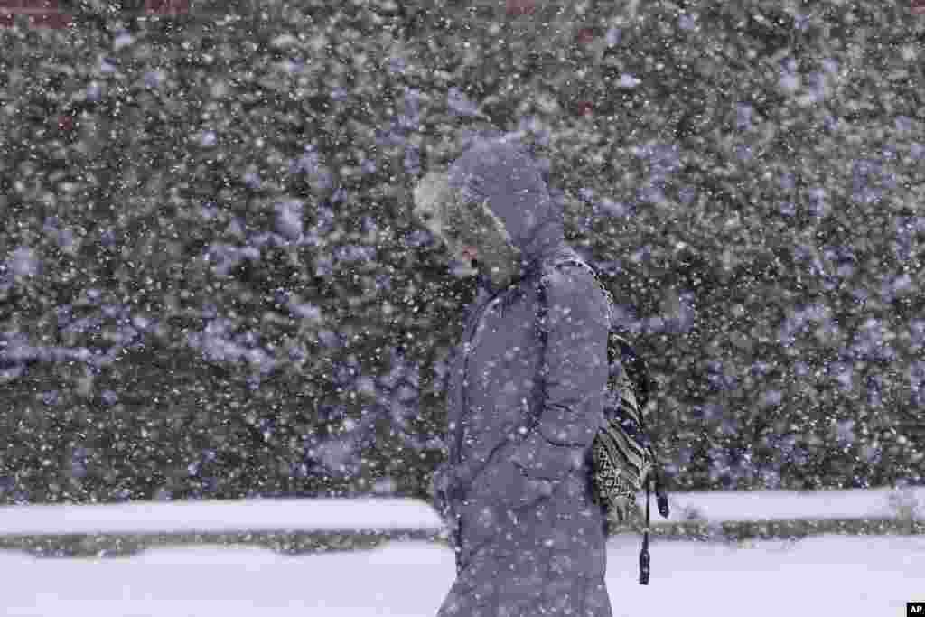 A pedestrian walks through a snow storm, in south Philadelphia, Pennsylvania, USA. The National Weather Service said the storm could bring 8 to 12 inches of snow to Philadelphia and New York City, and more than a foot in Boston.