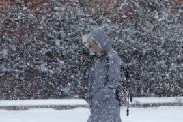 A pedestrian walks through a snowstorm, Jan. 21, 2014, in south Philadelphia.
