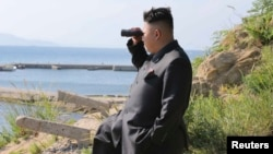 FILE - North Korean leader Kim Jong Un looks through a pair of binoculars during an inspection of the defense detachment on Ung Islet, in an undated photo released by North Korea's Korean Central News Agency in Pyongyang July 7, 2014.