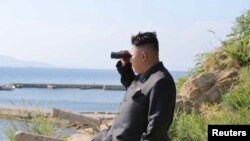 North Korean leader Kim Jong Un looks through a pair of binoculars during an inspection of the defense detachment on Ung Islet, in an undated photo released by North Korea's Korean Central News Agency on July 7, 2014.